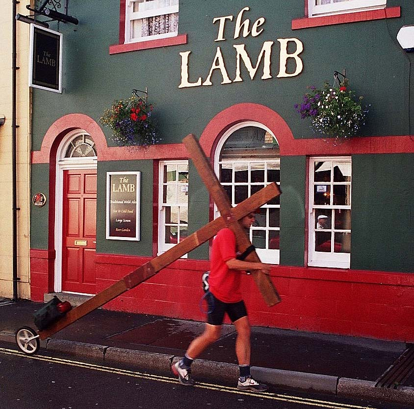 Counties evangelist Clive Cornish walking the cross by The Lamb pub in Builth Wells, Wales
