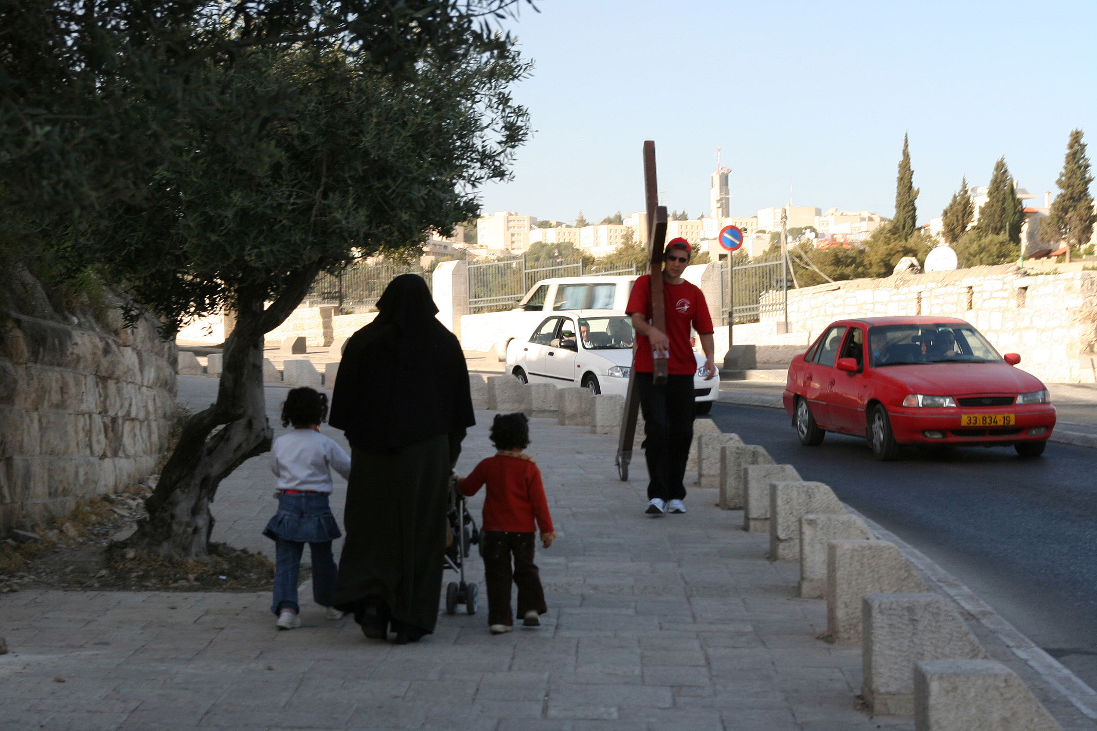 Counties evangelist Clive Cornish walks with his cross through Jerusalem close to the Mount of Olives. A Muslim family pass by during a project called From Jerusalem to Rome in the Footsteps of the Apostle Paul.