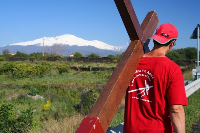 Counties evangelist Clive Cornish carries his cross past the volcano Mount Etna, Sicily - photographed during a project called From Jerusalem to Rome in the Footsteps of the Apostle Paul.