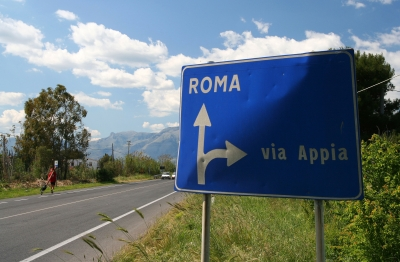Counties evangelist Clive Cornish walks past a sign to Rome and the Via Appia with his cross - photographed during a project called From Jerusalem to Rome in the Footsteps of the Apostle Paul.