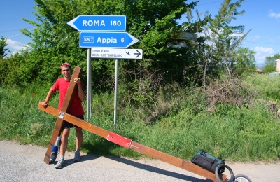 Counties evangelist Clive Cornish stops with his cross by a sign to Rome and the Via Appia - photographed during a project called From Jerusalem to Rome in the Footsteps of the Apostle Paul.
