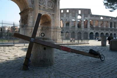 A Christian cross with the coliseum behind - photographed during a project called From Jerusalem to Rome in the Footsteps of the Apostle Paul.