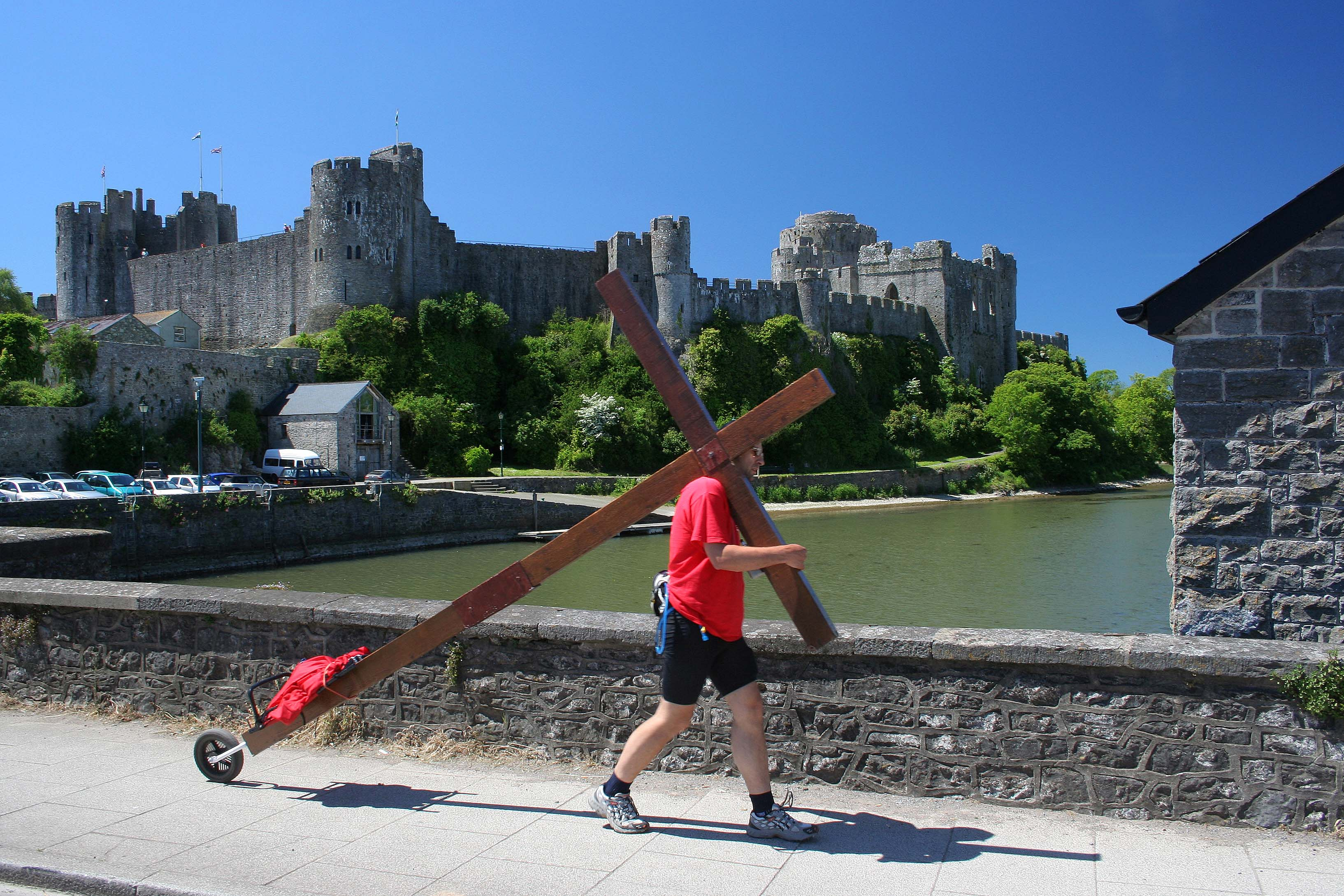 Counties evangelist Clive Cornish walking past Pembroke Castle with his cross. The magnificent medieval castle is viewed behind Clive as he crosses the West Wales river.