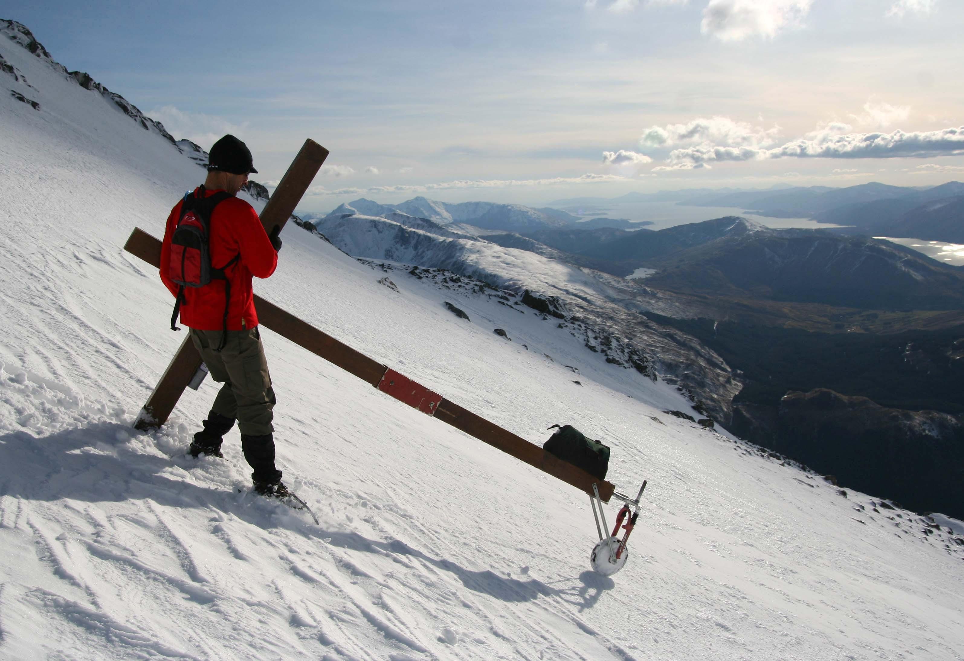 Counties evangelist Clive Cornish climbing Ben Nevis, Britain's highest mountain, in deep snow with his cross
