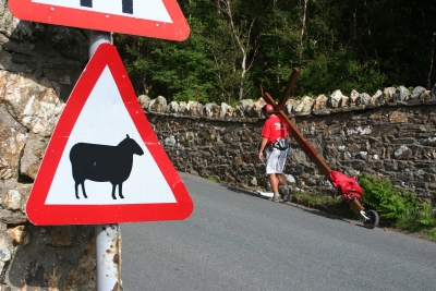 "Counties evangelist walks with a cross and passes a warning roadsign saying ""Beware sheep"""