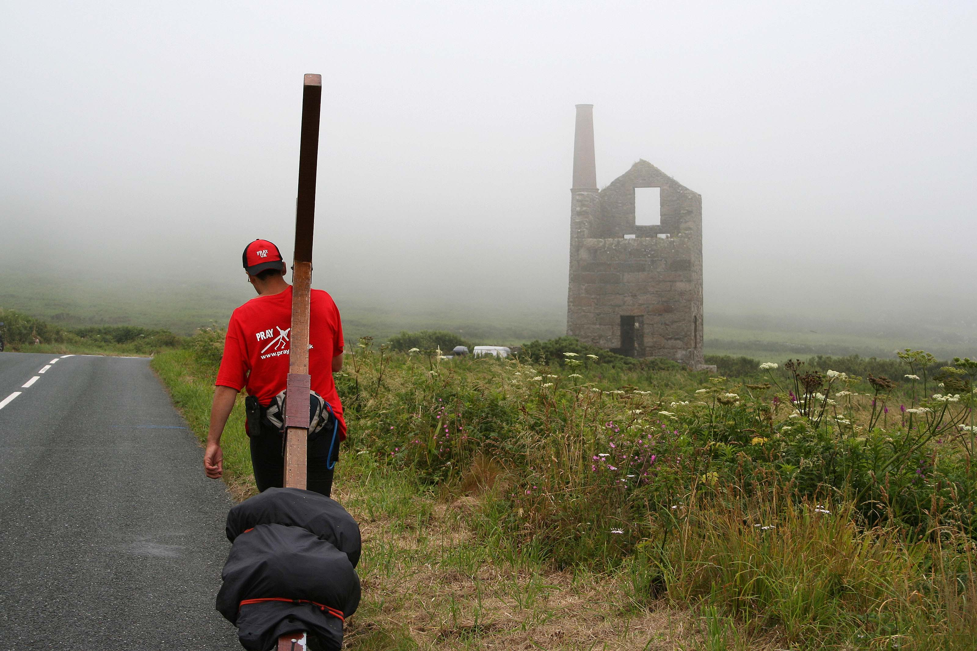 Counties evangelist walks with his cross towards a ruined tin mine in Cornwell - the tin mine looms out of the mist