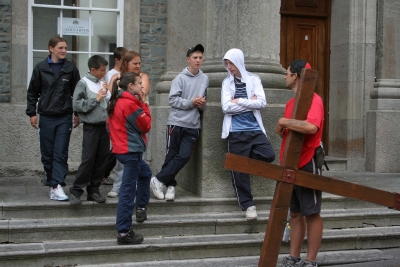Counties evangelist Clive Cornish stops while carrying his cross to talk with a group of young people outside Caernarfon Magistrates Court