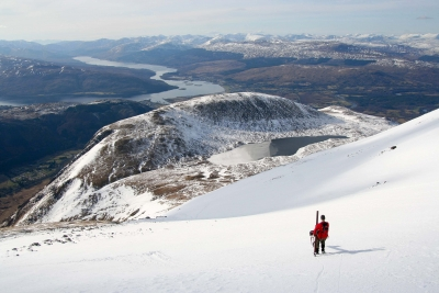 Counties evangelist Clive Cornish climbing Ben Nevis - Clive and his cross high on a snow slope with Scotland's mountains disappearing in to the distance
