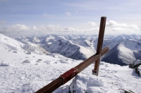 Counties evangelist Clive Cornish's cross near the summit of Ben mountain with distant mountain views of Scotland's snowy peaks
