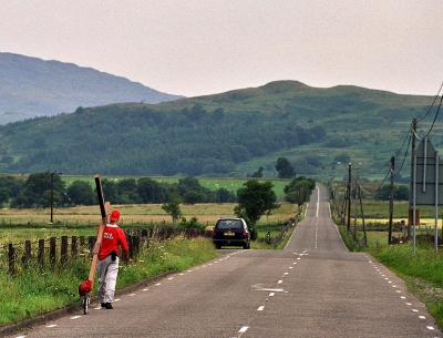 Counties evangelist Clive Cornish walks with his cross along a straight road near Cader Idris in Snowdonia