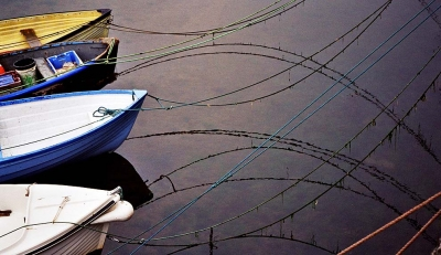 Boats moored in the Old Harbour, Fishguard, Wales. The mooring ropes and their refections make repeating fish shapes - the fish is a Christian symbol