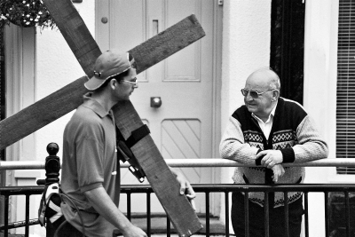A surprised man leans against a roadside railing and watches as Clive walks by with his cross
