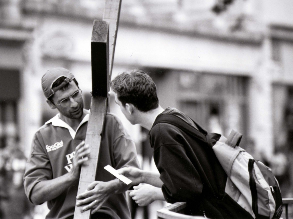 Counties evangelist Clive talks over a roadside railing with an interested young man - why are you carrying a cross