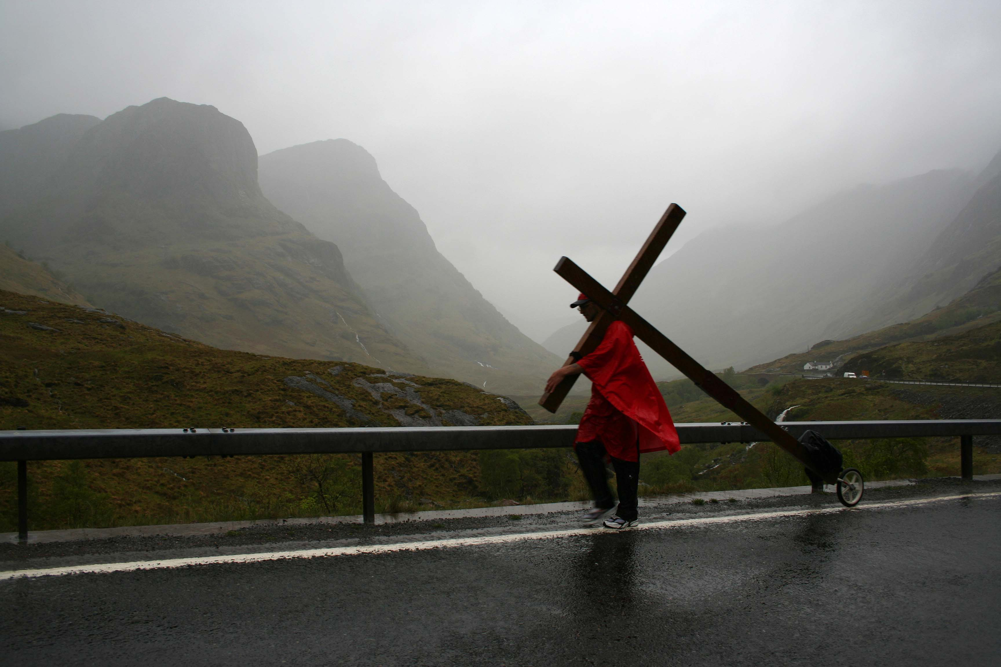 Counties evangelist Clive Cornish walks with his cross through a very wet Glencoe - he passed through Glencoe while walking from John O'Groats to Land's End