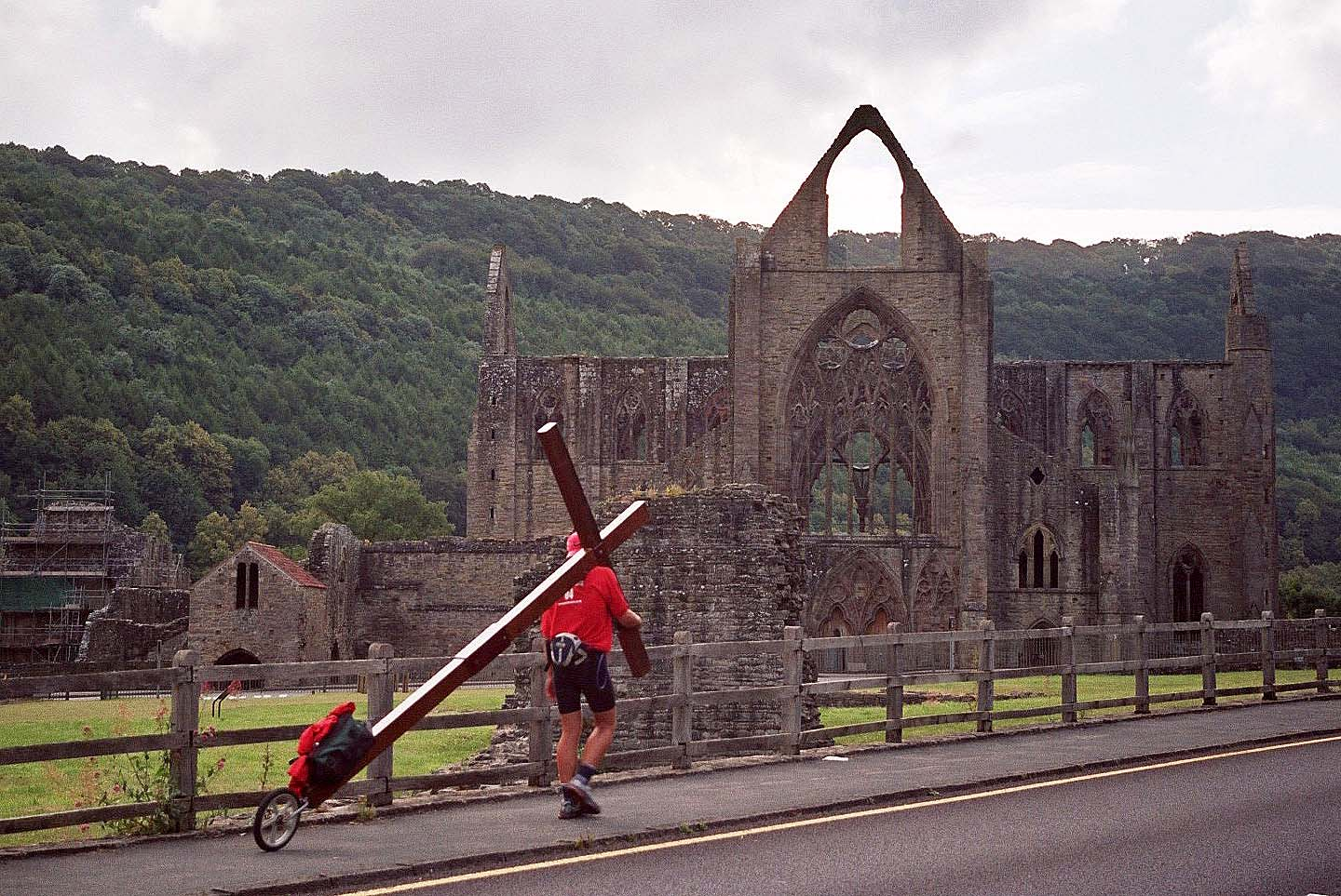 Counties evangelist Clive Cornish walks with his cross towards the ruins of Tintern Abbey in the Wye Valley