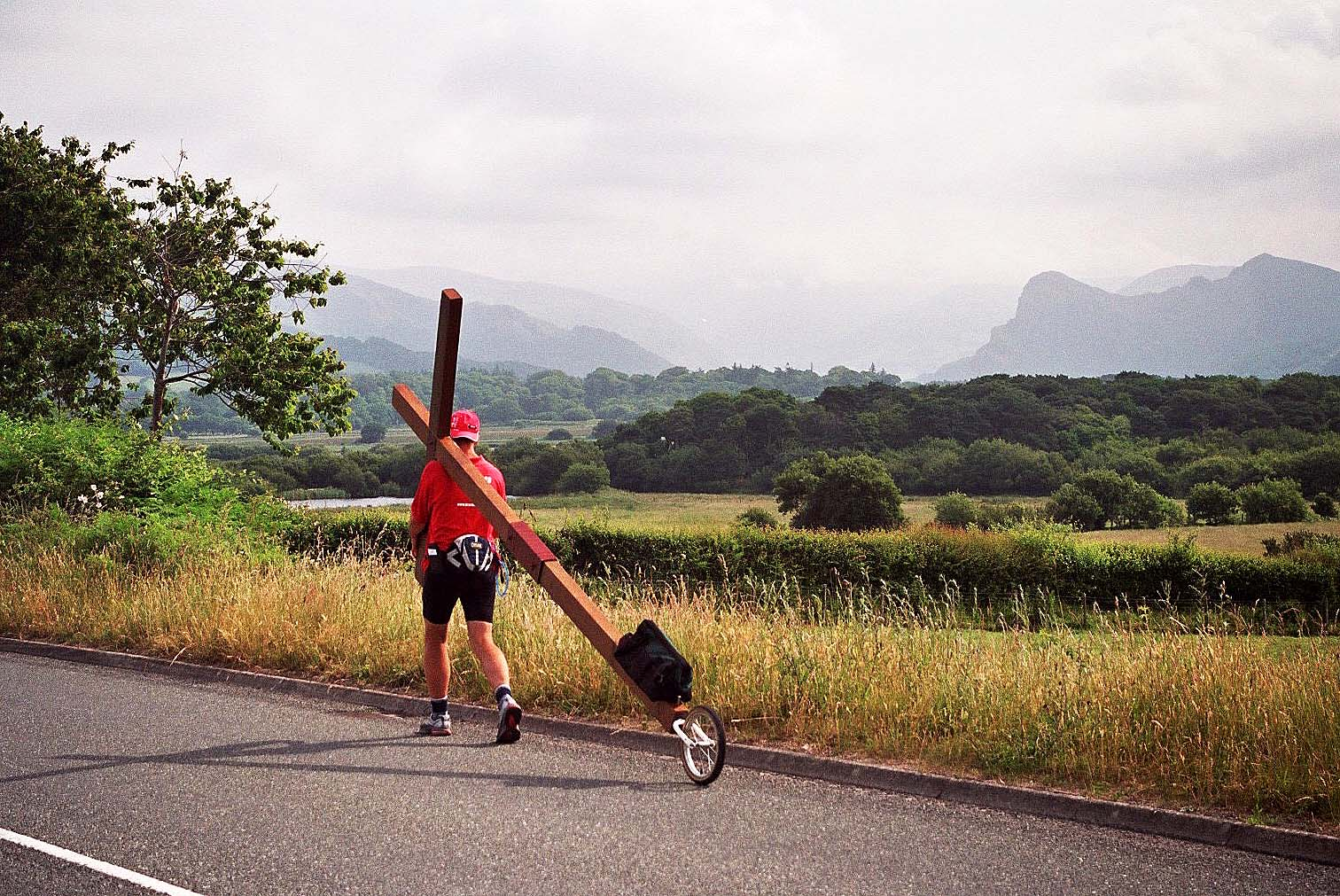 Counties evangelist Clive Cornish carries his cross in Snowdonia, North Wales. Bird Rock near Barmouth can be seen behind