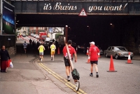 "Counties evangelist Clive Cornish runs with his cross during the Cardiff Half Marathon. Running under the bridge advertising says,""It's Brains you want!"""